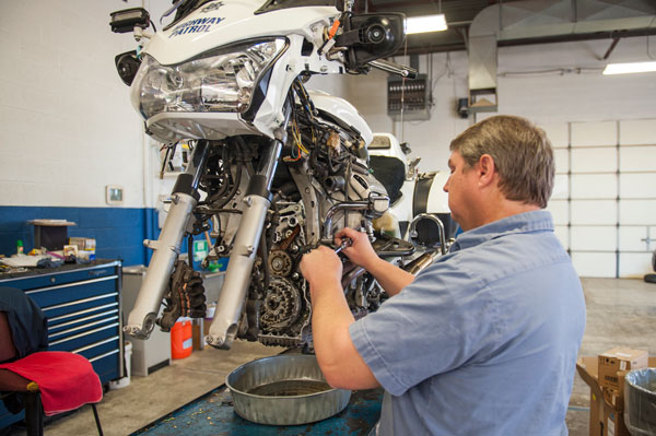 A DPS fleet technician can be seen here working on a DPS motorcycle.